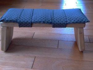 Un petit bans pliant pour la position assis-à genoux.